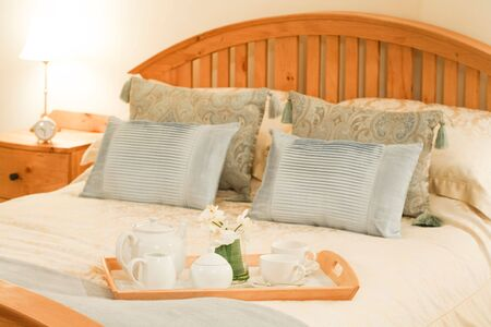 tea cosy: Room service tray on a bed in a luxury hotel bedroom with cozy bedlinen