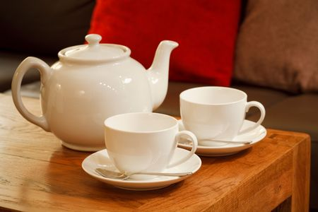 White china teapot and teacups with saucers in the living room of a modern home photo