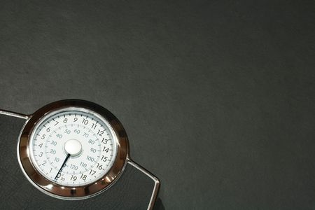 Bathroom scales on a dark slate floor with plenty of copy space Stock Photo - 6483206