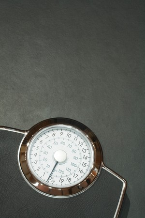 Bathroom scales on a dark slate floor with plenty of copy space. Ideal to illustrate dieting concept photo