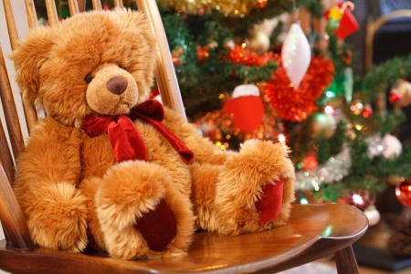 soft toy: Traditional Christmas scene with a teddy bear on a chair in front of a christmas tree Stock Photo
