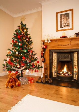 mantelpiece: Living room with christmas decorations, a fireplace and christmas tree. [Note: Picture above fireplace is photographers own work] Stock Photo
