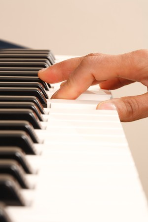 One hand playing on a piano keyboard photo