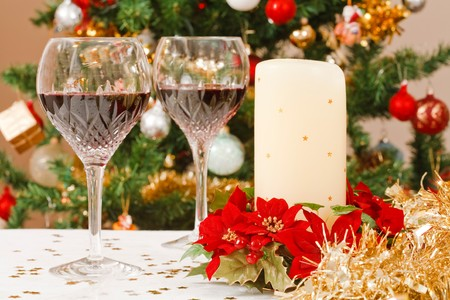 Christmas dining scene with tree, crystal wine glasses and christmas table decorations photo