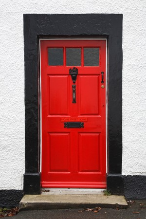 letterbox: Front door of a traditional british house painted bright red and with a Home Sweet Home sign