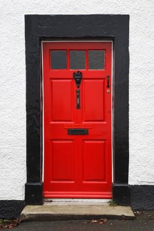 Vor der Tür eines traditionellen britischen Hauses hellrot lackiert und mit einem Home Sweet Home-Schild Standard-Bild