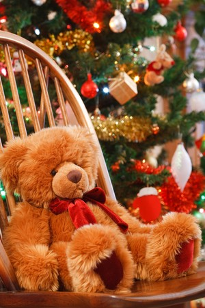 soft toy: Christmas interior with a teddy bear on a chair in front of a christmas tree