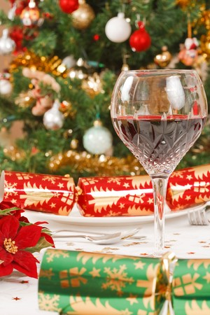 Chistmas crackers, christmas tree and a crystal glass with wine on a dining table Stock Photo - 7989787