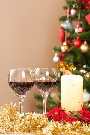 Dining room with festive decorations, christmas tree and crystal wine glasses photo