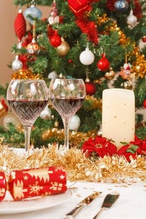 Dining table with christmas crackers, and decorations in front of a christmas tree Stock Photo - 7989814