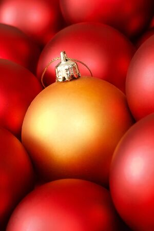 Closeup of gold christmas decoration surrounded by red baubles photo