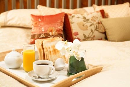 Bandeja de desayuno con café de la mañana en un dormitorio de lujo
