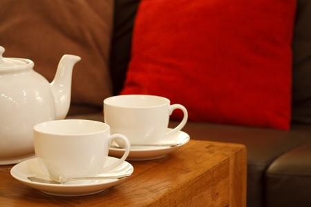 Teapot and cups in a contemporary lounge setting photo