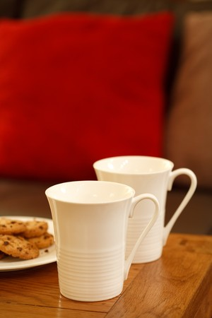 Coffee mugs and cookies with copyspace in a modern living room Stock Photo - 8145404