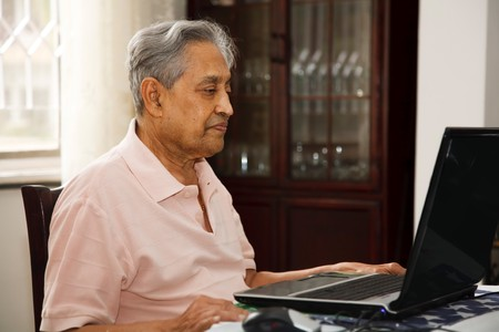 Elderly Indian man using a laptop computer at home photo