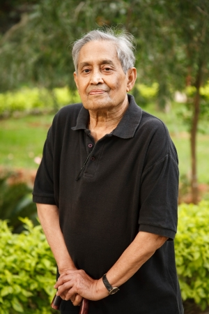 Elderly Indian Asian man stands in a park with a walking stick photo