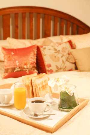 Breakfast tray with coffee, toast and orange juice on a luxury bed Stock Photo - 8682212