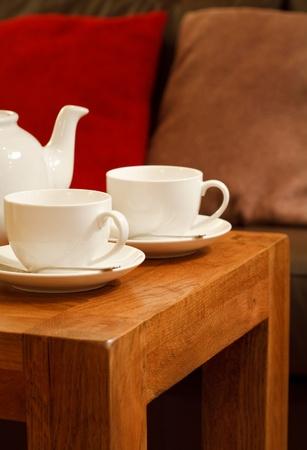Detail of a modern home interior with coffee table, teapot and teacups photo
