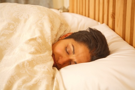 Asian Indian woman sleeping in a luxurious bed photo