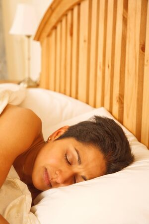 An attractive young Indian woman asleep in a luxury bedroom photo