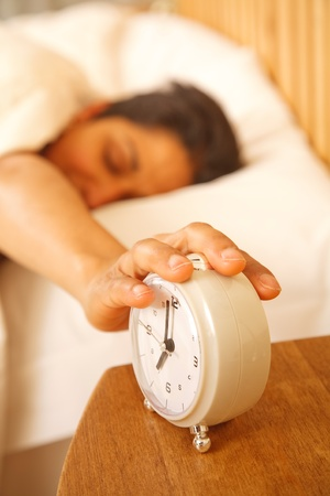 An Indian Asian woman wakes up to turn off a traditional alarm clock Stock Photo - 8682215
