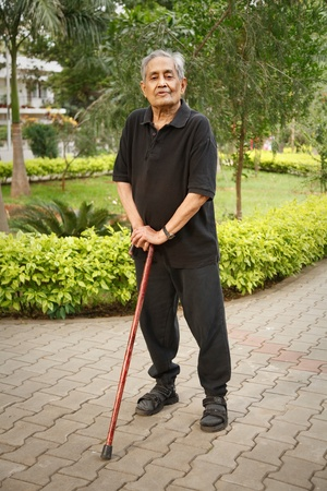 Old Indian Asian man stands in a park with a walking stick