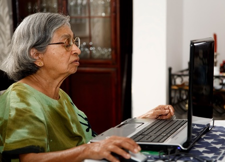 use computer: Elderly Asian Indian woman uses a laptop computer at home