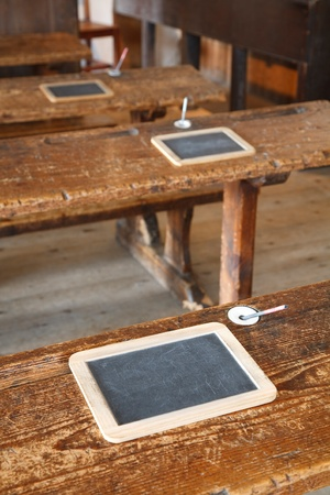 schoolhouse: Ancient classroom with traditional wooden benches and slate tablets Stock Photo