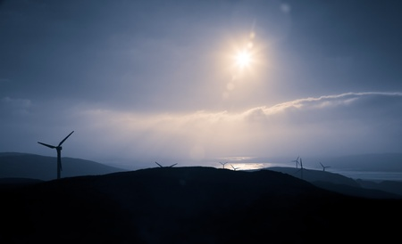 Wind farm on the west coast of Britain silhouetted by the setting sun photo