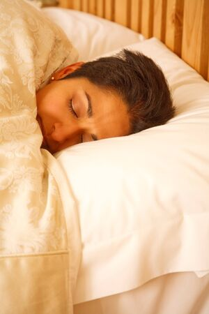 A young Indian woman looking very cozy asleep in bed Stock Photo - 9027498