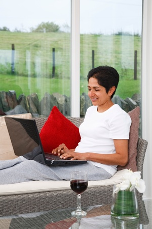 office use: Young Indian Asian woman relaxes using the internet at home