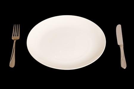 banqueting: White plate with knife and fork isolated on a black background. With clipping path