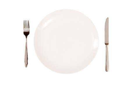 knife and fork: White plate with knife and fork isolated on a white background.