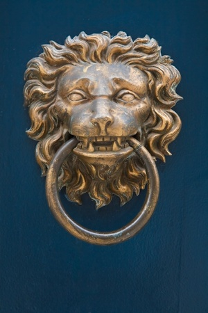 handle: Traditional brass door knocker in the shape of a lions head against a blue painted door