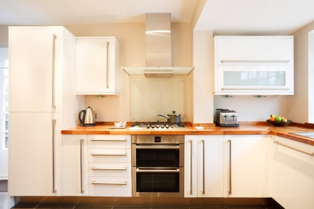 stainless steel kitchen: Modern white kitchen with wooden worktops and stainless steel appliances