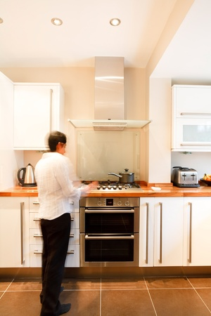 Indian Asian woman in a stylish modern kitchen with white units and a wooden worktop photo