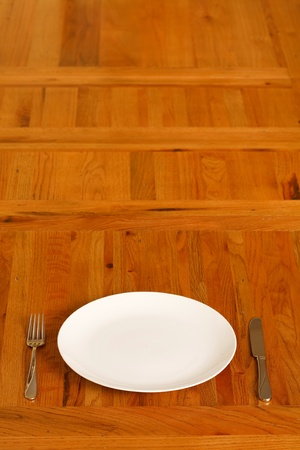 one item: Wooden table with a single plate and cutlery. Lots of space for copy. Stock Photo