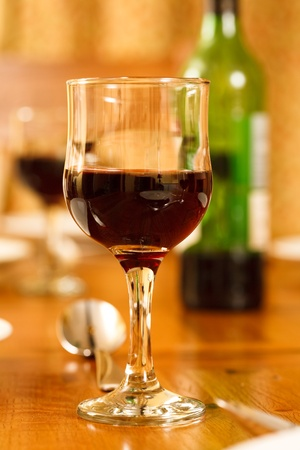 banqueting: Glass of red wine on a dining table with a bottle of wine and more glasses in the background