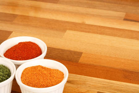 worktop: Bowls of spice on a wooden kitchen worktop Stock Photo