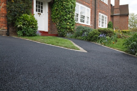 New bitumen driveway outside a beautiful brick house in London. Plenty of space for text. photo
