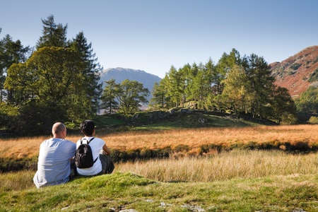 A mixed race couple enjoy a scenic view in Borrowdale, Lake District, Cumbria, UK. Caucasian man, Indian Asian woman. photo