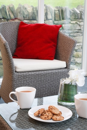 showhome: Coffee and cookies in a modern but cozy home interior with wicker furniture in a conservatory living room Stock Photo