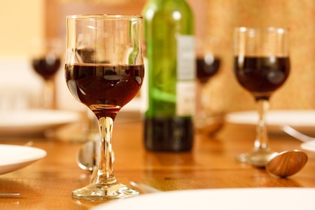 banqueting: Dining table with a wine bottle and glasses filled with red wine Stock Photo
