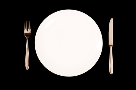 banqueting: Place setting with white plate, knife and fork isolated on a black background.