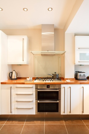 cooker: Modern white kitchen with wooden worktops and stainless steel appliances