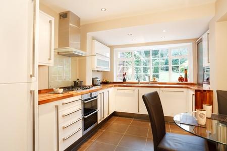 Contemporanea designer zona cucina e prima colazione con moderne unità di bianco e di elettrodomestici in acciaio inox