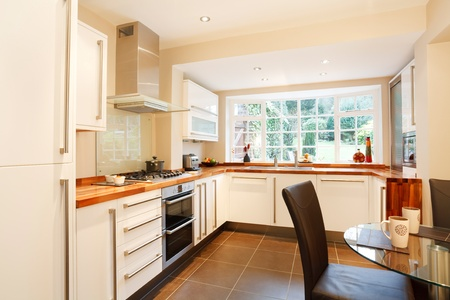 fitted: Contemporary designer kitchen and breakfast area with modern white units and stainless steel appliances