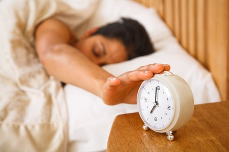 An Indian Asian woman wakes up and reaches to turn off a traditional alarm clock Stock Photo - 10550840