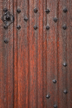 Detail of an ancient medieval wooden door with decorated wrought iron studs photo