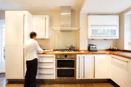 refurbishment: Indian Asian woman cooking in a stylish modern designer kitchen
